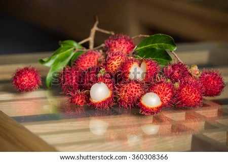 Rambutan fruit branch with leaves on the table - stock photo