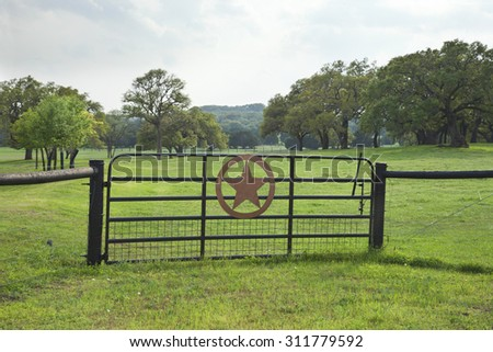 Ranch gate with a star in a Texas Hill Country pasture with trees - stock photo