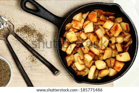 Ranch Potatoes in Cast Iron Skillet on Cutting Board with Black Pepper. - stock photo