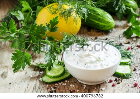 Ranch sauce in a white porcelain bowl with vegetables, herbs and spices on an old wooden table, selective focus - stock photo
