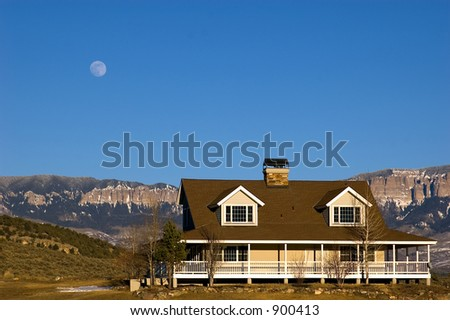 ranch style house with walk around porch full moon rising - stock photo
