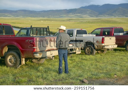 Rancher and cowboy looking at pickup trucks in Centennial Valley, near Lakeview, MT - stock photo