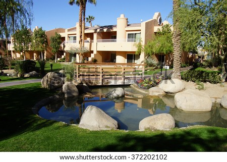 RANCHO MIRAGE, CALIFORNIA - DEC 16, 2015 - Southwestern style hotel buildings with ponds in green oasis with Palm trees,  Rancho Mirage, California - stock photo