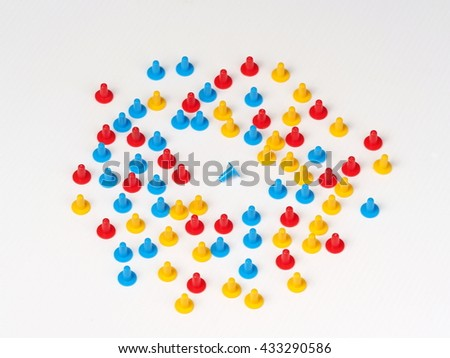 Random group colored plastic hat shaped parts red, blue and yellow on white with on tipped over blue one in the center - stock photo