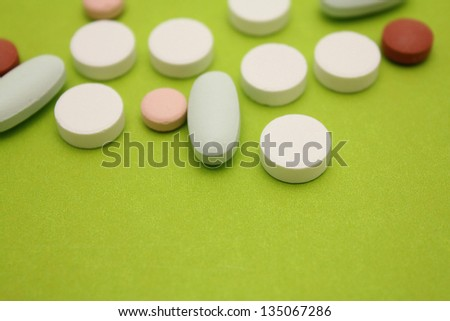 random loose pills over green background