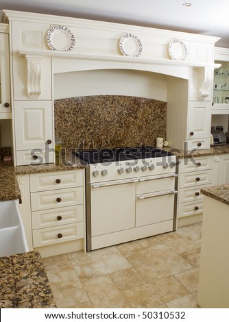 Range style cooker in a modern kitchen interior with granite worktop and cream units - stock photo