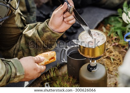 rangers team are heated food on the fire and eat in the forest
