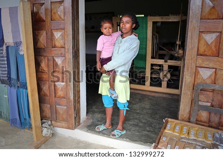 RANOMAFANA, MADAGASCAR - JAN 16: Young mother & baby stand in the doorway to textile shop on January 16, 2013 in Ranomafana, Madagascar.