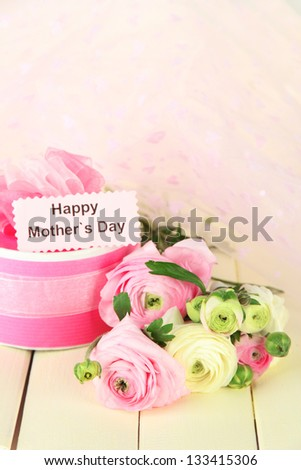Ranunculus (persian buttercups) and gift for mothers day, on white wooden background - stock photo