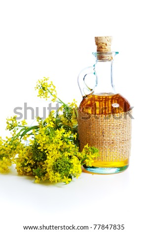 Rapeseed flower and oil in bottle - stock photo