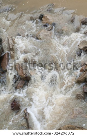 rapid flow of water in the river, visible stones - stock photo
