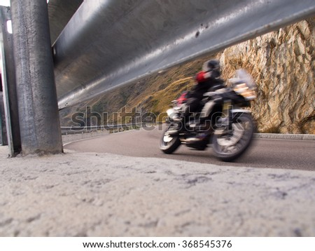 rapid motorcyclists from the roadside with guardrail - stock photo