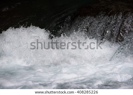Rapid water splashes of an white water river or stream. - stock photo