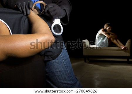 Rapist being arrested and identity of victim blurred in the background.  Intentional shallow depth of field to blur female in the background.  This is an illustrative editorial not real. - stock photo