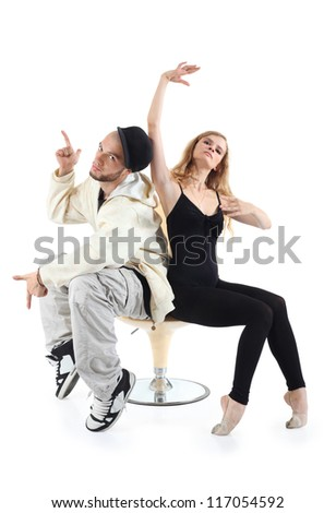 Rapper and ballerina sit on yellow chair and pose isolated on white background. - stock photo