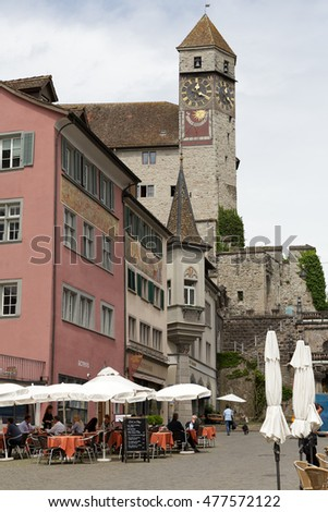 RAPPERSWIL, SWITZERLAND - MAY 10, 2016: Clock tower towering over the buildings of the city can be seen from the side of town square. Several people can be seen in a distance.