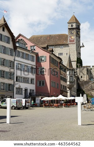 RAPPERSWIL, SWITZERLAND - MAY 10, 2016: The 13th century castle with a clock tower towering over the buildings of the city can be seen from the side of town square