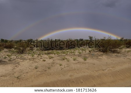 Rare double rainbow during a thundershower in the Kalahari Desert, South Africa. 9 frame exposure stack.  - stock photo