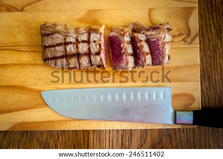 rare sliced beef rump steak and carving knife on a wooden chopping block with a dark wood background - stock photo