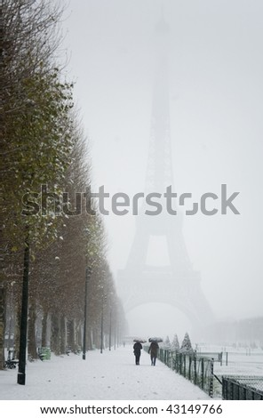 Rare snowy day in Paris. Misty Eiffel Tower, Champ de Mars and lots of snow - stock photo
