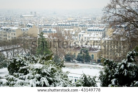 Rare snowy day in Paris. Parisian roofs covered with snow, view from the Montmartre hill - stock photo