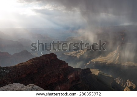 Rare spring shafts of snow lit by the evening rays of sunlight moving thru the Grand Canyon from the South Rim - stock photo