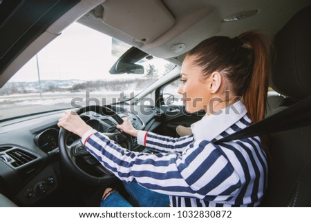 Rare view of young girl with brown hair driving car on a winter day.