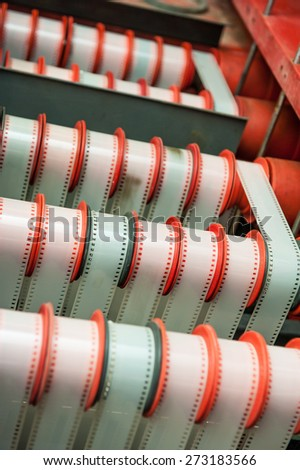 Rare vintage industrial cinema 35 mm movie film development machine, selective focus detail with film loaded in post production factory - stock photo