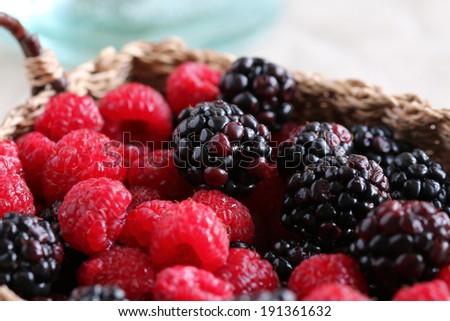 Raspberries and blackberries in wicker basket - stock photo