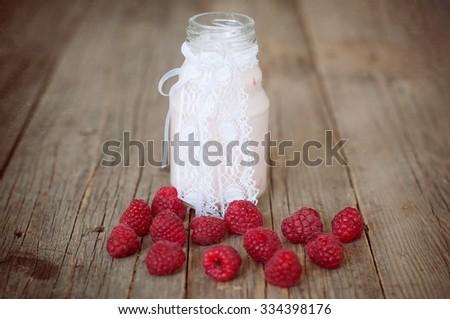 Raspberries in a little bottle on wooden table - stock photo
