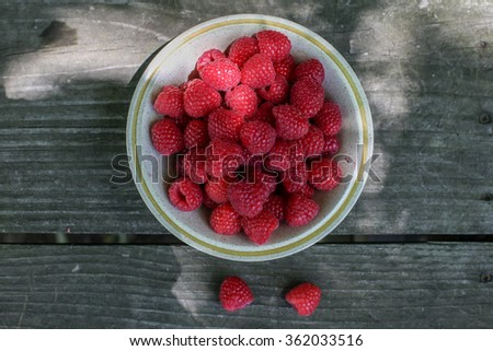 Raspberries in the bowl on wooden table - stock photo