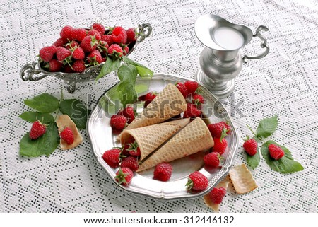 Raspberries in waffle cone with metal dish and milk
