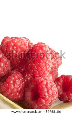 Raspberries on green dish isolated on white background - stock photo