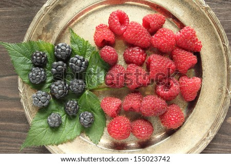 Raspberry and blackberry on a silver platter - stock photo