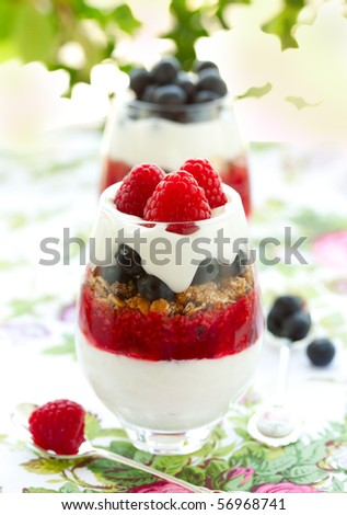 raspberry and blueberry parfait with cream and granola. - stock photo