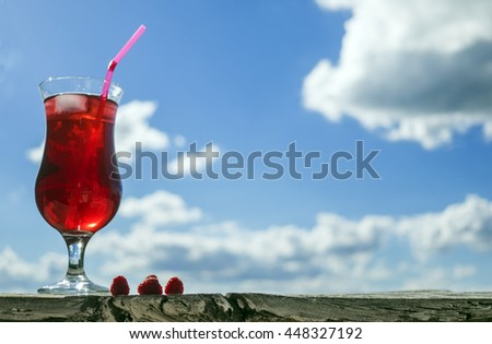 Raspberry and lemonade against blue sky with clouds - stock photo