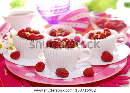 raspberry and pistachio cupcakes in white tea cup shape molds - stock photo