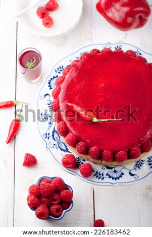 Raspberry and roast bell pepper  mousse cake, cheesecake with fresh chili pepper on a white wooden background - stock photo