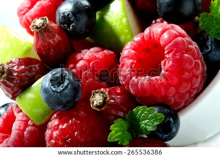 raspberry, blueberry, rosehip berries, apple pieces  and mint leaves close-up on white  - stock photo