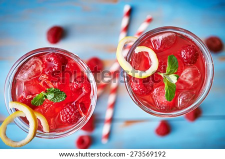 raspberry cocktail with lemon and mint shot from overhead view on rustic table top - stock photo