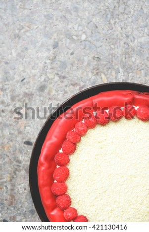 Raspberry cream mousse cheesecake with white chocolate topping and red fondant. Decorated with fruit. - stock photo