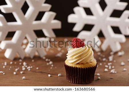 Raspberry cupcake on white snow flakes Christmas background - stock photo