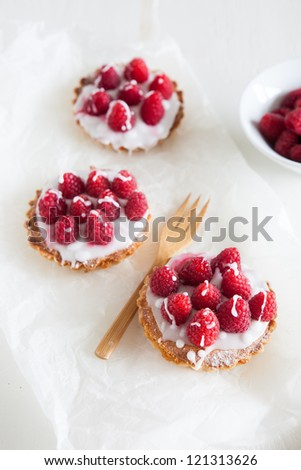 raspberry frangipane tarts with icing drizzled over the top - stock photo