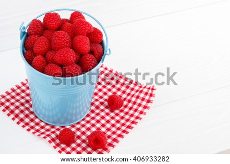 Raspberry in a blue bucket on white wooden table
