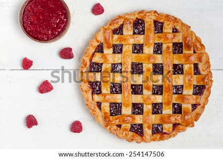 Raspberry pie with fresh raspberries and raspberry jam on white table. Top view - stock photo
