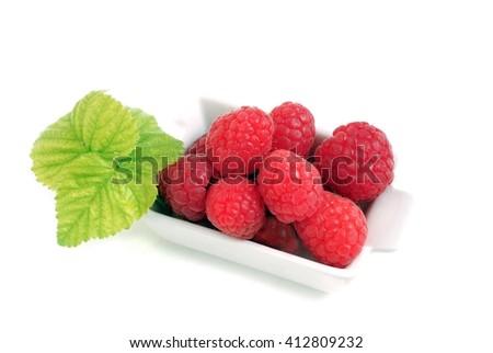 Raspberry. Sweet raspberry isolated on white background. Ripe red raspberry on white.  Raspberry with green leaves. Raspberry in white bowl. Delicious fresh raspberry.  - stock photo