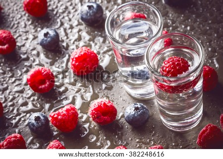 Raspberry vodka glass shot with fruit inside.