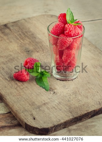 raspberry with mint in a glass Cup on wooden rustic background. summer harvest. toned image - stock photo