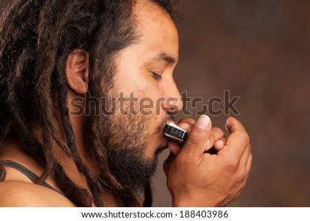 Rastafarian man playing mouth harmonica - stock photo
