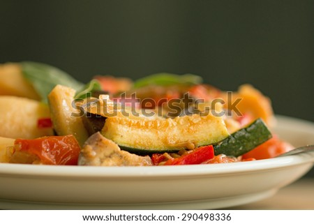 Ratatouille on white plate against dark background, closeup with selective focus